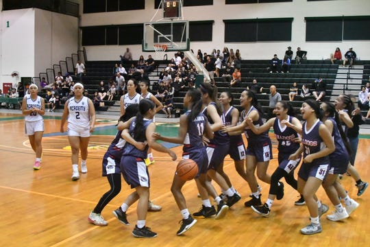 The Okkodo High School Bulldogs celebrate the last few seconds of their 46-39 semifinal overtime win against the Academy of Our Lady of Guam Cougars Dec. 11 at the University of Guam Calvo Field House. The Bulldogs will face Saint Paul on Dec. 14 for the championship.