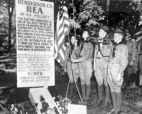 Members of Boy Scout Troop 13 raise a flag at a ceremony celebrating the first power pole erected as Henderson County REA prepared to bring the first electric service to some 1,200 farms and farm homes here on May 19, 1937. The ceremony in Atkinson Park included a ceremonial burial of an old oil lamp. Henderson County REA was the first co-op in the state. Its first customer was Frank T. Street of Cardinal Farms, south of Henderson. (Photo courtesy of Kenergy)