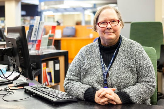 Maeve Clark, adult services coordinator at the Iowa City Public Library, poses for a photo, Thursday, Dec. 12, 2019,  at the information desk on the second floor at the Public Library in Iowa City, Iowa.