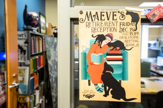 A poster celebrating Maeve Clark's retirement hangs up outside her office, Thursday, Dec. 12, 2019, at the Public Library in Iowa City, Iowa.