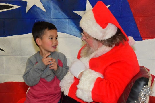 Lucas Stanley, 5, visits with Santa telling him all his Christmas wishes at Christmas in Karns held at Karns Elementary School Saturday Dec. 7.