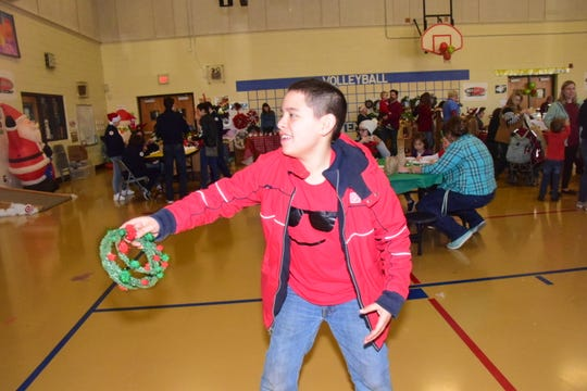 Bryson McCall, 12, throws a wreath onto a peg at the JrROTC game table at Christmas in Karns held at Karns Elementary School Saturday Dec. 7.