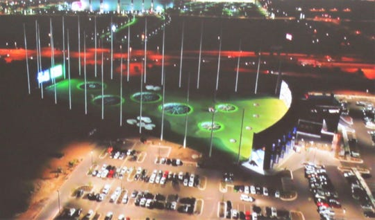 A depiction of the Topgolf site on Outlet Drive shows the lighted driving range during evening hours; the main building to the right will hold restaurants, bars and game areas.