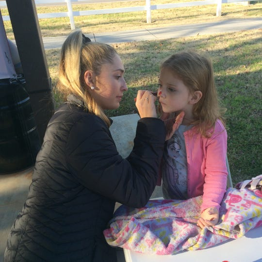 Summer Parker of Powell carefully applies face paint to 4-year-old Maddox Hudson of Powell.