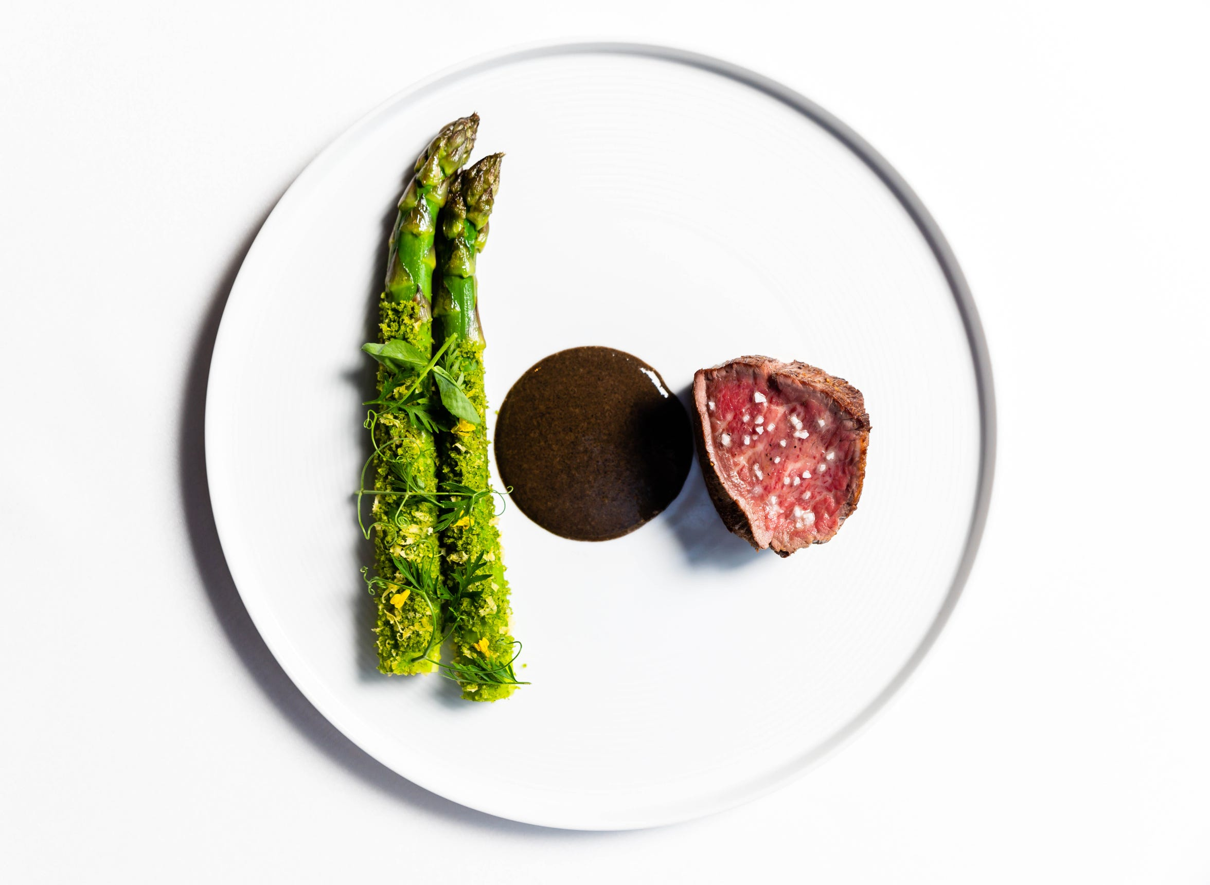 Beef, asparagus, cured egg yolk, chard, onion bordelaise as served at Restaurant Eugene in May 2019, shortly before the restaurant closed after 15 years of operations. (Courtesy Hopkins & Co.)