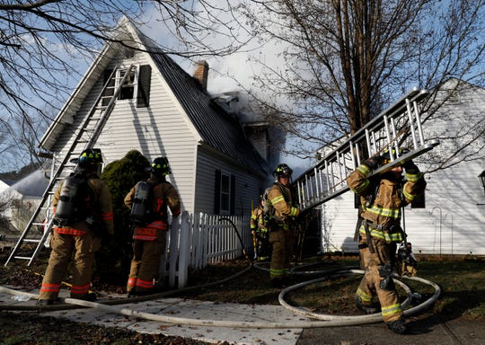 Firefighters from four area departments fight a house fire Thursday morning, Dec. 12, 2019, on Oak Street in Bremen.