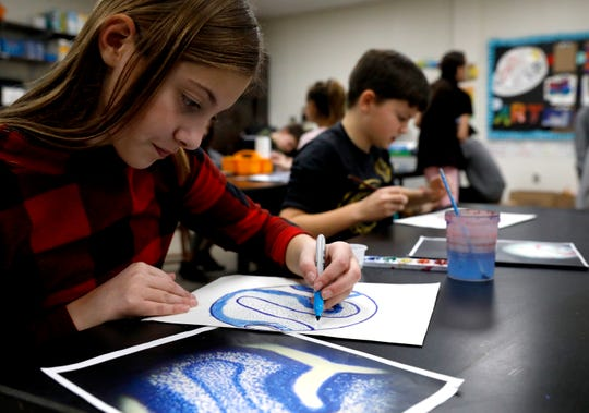 Lily Bates, left, uses a marker to add details to her drawing Thursday, Dec. 12, 2019, at Mount Pleasant Elementary in Lancaster. Bates and other fifth graders at the school were working on art work based off of photographs taken through microscopes by Lancaster High School students.