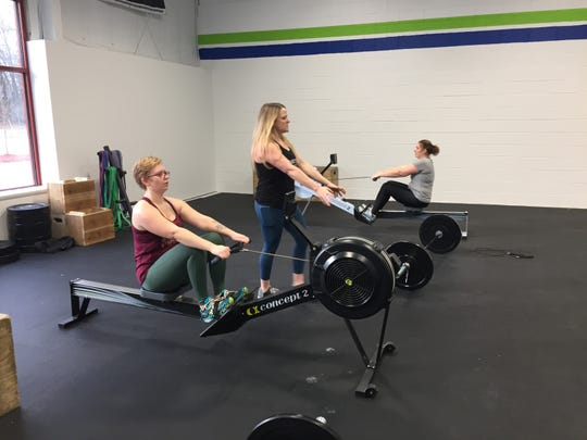 Diana Netherton, center, instructs fitness students Heidi Blake, left, and Alisa Harwell as they work out on rowing machines at Grand Trunk CrossFit in Hartland Township, Thursday, Dec. 12, 2019.