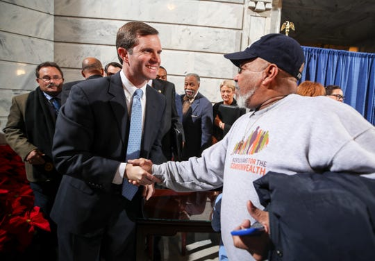 Juan Gomez, right, shakes the hand of Gov. Andy Beshear on Dec. 12, 2019, after the governor signed an order restoring voting rights to thousands of non-violent felons who had completed their sentences. Gomez was convicted of burglary 15 years prior and served two years in prison.