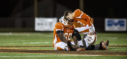 DeSales wide receiver Jason Higdon (22) consoles teammate Cassius Britt (60) after the Colts fell to Belfry in double-overtime in the Class 3A state semifinal game. Nov. 29, 2019