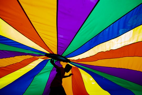 Children play underneath a colorful parachute during a Field Day at Cane Run Elementary School as students get through their last week of school before summer. June 5, 2019