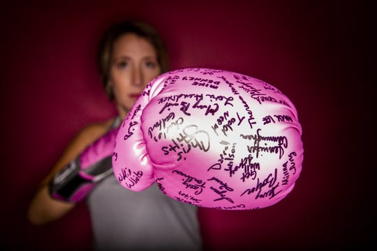 Cancer survivor Sara Westerman poses with the pink boxing gloves given to her by her coworkers at the Kentukcy Lottery.