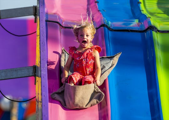 A young girl screams her way down the 'Fun Slide' in the Thrill Ville area of the 2019 Kentucky State Fair. Aug. 15, 2019