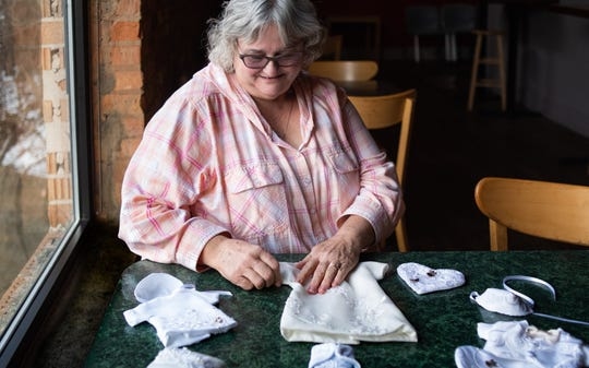 """Bonnie Kalahar talks about the """"angel gowns"""" she creates from recycled wedding dresses for stillborn babies, Wednesday, Dec. 11, 2019, during an interview at Sir Pizza in Lansing's Old Town. Grieving parents are also given a heart-shaped memento or pillow made from the same cloth adorned with an angel pendant and wings."""