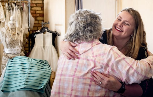 """Lindsey King, right, owner of The Dowry Bridal Salon in Lansing hugs Bonnie Kalahar Wednesday, Dec. 12, 2019. King donates used bridal dresses to Kalahar, who cuts them up and uses them to make """"angel gowns"""" for stillborn babies when presented to grieving parents."""