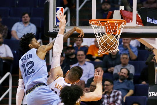 Memphis Grizzlies guard Ja Morant (12) dunks over Phoenix Suns center Aron Baynes during the second half of an NBA basketball game, Wednesday, Dec. 11, 2019, in Phoenix. The Grizzlies defeated the Suns 115-108. (AP Photo/Ross D. Franklin)