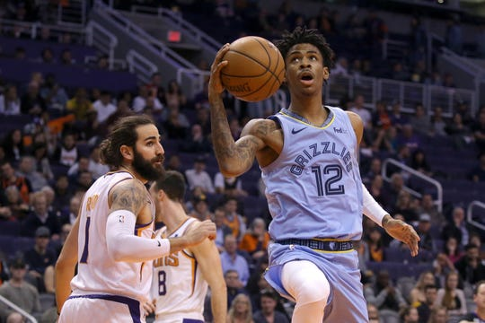 Memphis Grizzlies guard Ja Morant (12) drives past Phoenix Suns guard Ricky Rubio, left, during the first half on Wednesday, Dec. 11, 2019 in Phoenix.