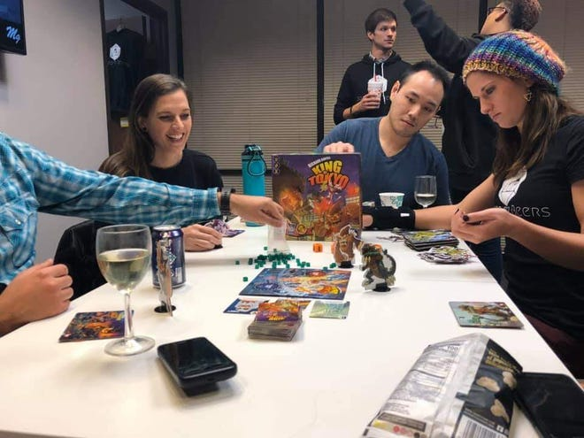 Taylor Herndon (right), plays King of Tokyo during a pop up board game night. Herndon, 27, hopes to open board game bar Board to Beers in January if a Kickstarter fundraiser is successful.