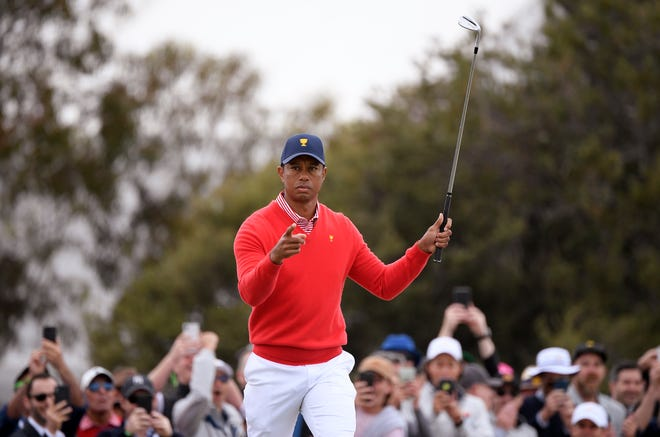 Tiger Woods points after winning the fifth hole with a birdie during an opening fourball match at the Royal Melbourne Golf Club in the President's Cup golf tournament Thursday.