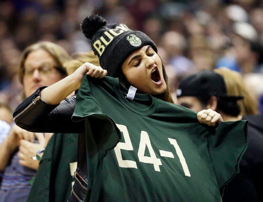 "Mallory Edens, daughter of Bucks co-owner Wes Edens, holds up a ""24-1"" shirt during the second half of the game between the Milwaukee Bucks and the Golden State Warriors on Dec. 12, 2015."