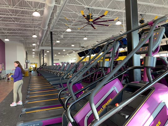 Amber Crider, club manager of Planet Fitness in Waukesha, works out operational details with her new staff during the gym's opening week in early December. The 20,000-square-foot fitness center joins an unusually long list of gyms in the city.