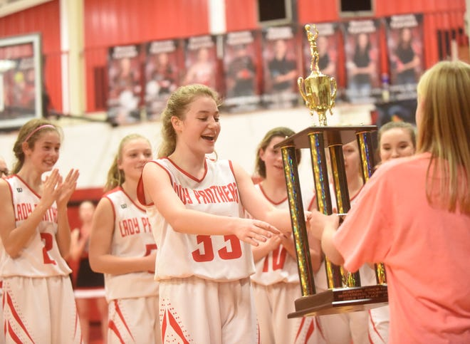 Norfork's Kiley Alman and other members of the Junior Lady Panthers prepare to lift the Norfork Junior Invitational championship trophy on Wednesday night.