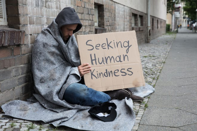 Homeless man soliciting money on the street.