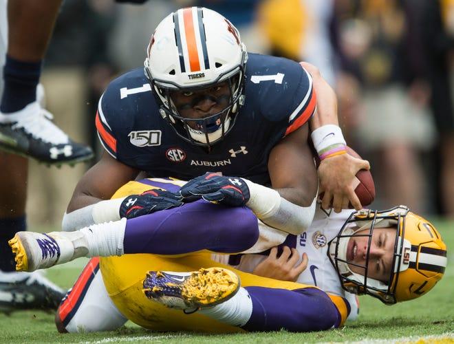 Auburn defensive lineman Big Kat Bryant (1) jumps on LSU quarterback Joe Burrow (9) for a sack at Tiger Stadium in Baton Rouge, La., on Saturday, Oct. 26, 2019. LSU defeated Auburn 23-20.