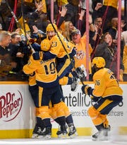 Nashville Predators right wing Craig Smith (15) celebrates his game-winning goal with center Calle Jarnkrok (19), center Rocco Grimaldi (23), and defenseman P.K. Subban (76), during the overtime period of the divisional semifinal game at Bridgestone Arena in Nashville, Tenn., Wednesday, April 10, 2019.
