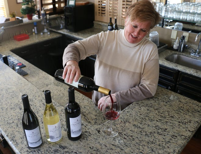 Carrie Drury pours a glass of wine in her office on Ninth Avenue North in Franklin on Dec. 12, 2019.