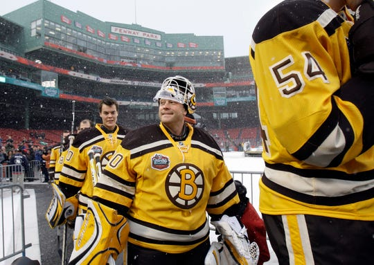 Boston Bruins players including goalie Tim Thomas, center, walk to the ice rink to practice at Fenway Park in Boston on Thursday, Dec. 31, 2009, in preparation for New Years Day's Winter Classic NHL hockey game against the Philadelphia Flyers. (AP Photo/Elise Amendola)