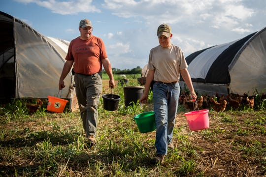 Jim Vaughn, left, and his son Caleb Vaughn, 12, head home after collecting eggs at Rocky Glade Farm in Eagleville, Tenn., on Aug. 22, 2019.