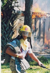 Retiring Chief Joseph Daigle battling a house fire in 2000.