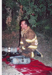 Chief Greg DeWitt changing air tanks during a house fire in 1996.