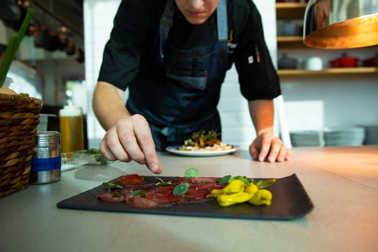 Corporate chef Jason Goddard puts the finishing touches on a carpaccio dish, Wednesday, Dec. 11, 2019, at Grappino in Naples.