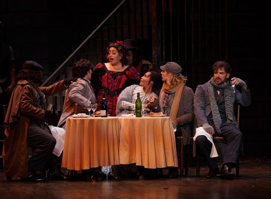 Musetta (Marlen Nahhas, standing) charms the table, including Mimi (Lauren Michelle) and Rodolfo (Matthew White) as her jealous ex-lover Marcello (Craig Verm) broods.