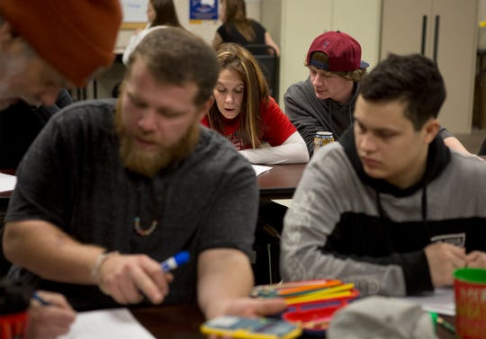 Noah Moore, 23, (red hat) talks with fellow classmate, Lynsay Lewis, about a math problem they are trying to solve in day reporting's GED program. Moore has completed the day reporting program and graduated but returns each week so he can work on his GED requirements.