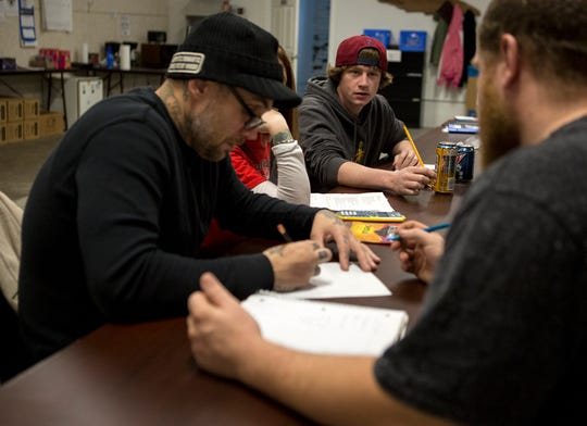 Noah Moore, 23, (red hat) talks with fellow classmates in day reporting's GED program. Moore has completed the day reporting program and graduated but returns each week so he can work on his GED requirements.