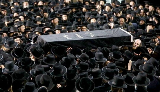 The casket of Moshe Hirsch Deutsch is carried to a hearse as thousands of Orthodox Jewish men crowded Rodney Street in Williamsburg, Brooklyn Wednesday night for the funeral Deutch, one of the victims of the fatal shooting in Jersey City.
