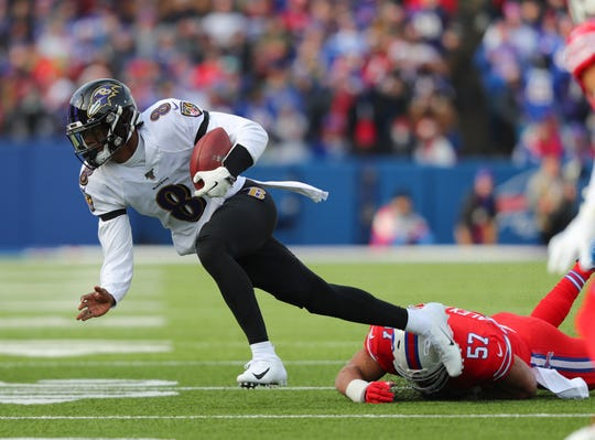 Lorenzo Alexander #57 of the Buffalo Bills dives to make a tackle on Lamar Jackson #8 of the Baltimore Ravens as he runs the ball during the first quarter at New Era Field on December 8, 2019 in Orchard Park, New York.