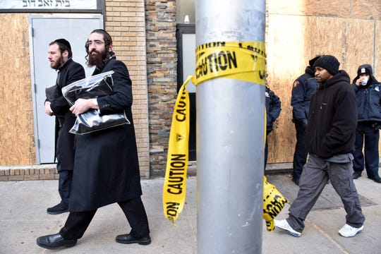 Two Orthodox Jewish men walk past the Jersey City Kosher Supermarket two days after a shootout in Jersey City, N.J. on Thursday Dec. 12, 2019. One police officer, three civilians and the two shooters and were killed.