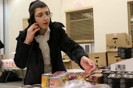 Nachman Nusson Berdugo, 13, of Jersey City, is shown as he obtains food for Shabbos.  After the mass shooting on Tuesday, the orthodox Jewish community in Jersey City was left without a place to shop for kosher food. Met Counil, a large kosher food corporation, which has a charitable organization, decided to donate free food to the community through a partnership with the  Jersey City Health and Human Services department.  Met Council donated free food to the community. Thursday, December 12, 2019