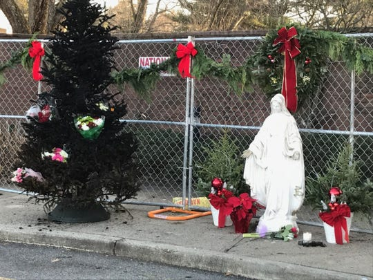 Charred Giving Tree stands next to Virgin Mary statue in front of chain link fence barrier near entrance to the Most Blessed Sacrament Church where parishioners gathered Thursday to hold vigil for the structure, destroyed by fire Tuesday night.