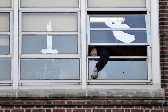A contractor removes a window with a bullet hole in it from a classroom at the Sacred Heart School which is located across the street from the Jersey City Kosher Supermarket two days after a shootout in Jersey City, N.J. on Thursday Dec. 12, 2019. One police officer, the two shooters and three civilians were killed.