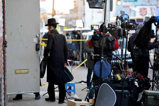 An orthodox jewish man walk into the synagog, past members of the media set up outside of the Jersey City Kosher Supermarket two days after a shootout in Jersey City, N.J. on Thursday Dec. 12, 2019. One police officer, the two shooters and three civilians were killed.