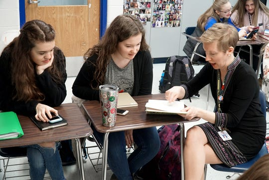 Lakeland High School teacher Kathleen Miska sits down with students Louisa Gross, left, and Kara Hance on March 25 to discuss some in-class reading options.