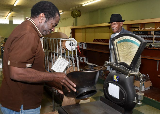 Store employee Joseph Boast weighs a sale of nails for one more customer, Fred Darby, Wednesday afternoon. Boast has 30 plus years of employment at J. B. Sandoz.