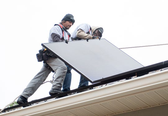 From left, Mainrel Hernadez and Terell Odom, of Compass Solar Energy, install a solar panel on a house in Milton on Dec. 11.