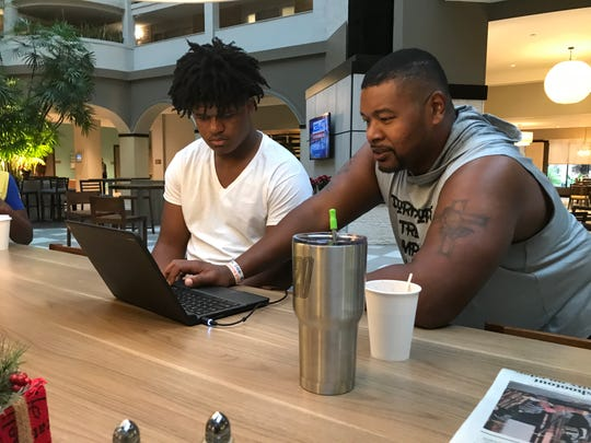 Escambia senior Xavier Johnson (left) works on homework with the help of assistant coach Erik Lee on Thursday monring in Jacksonville in the hotel lobby.