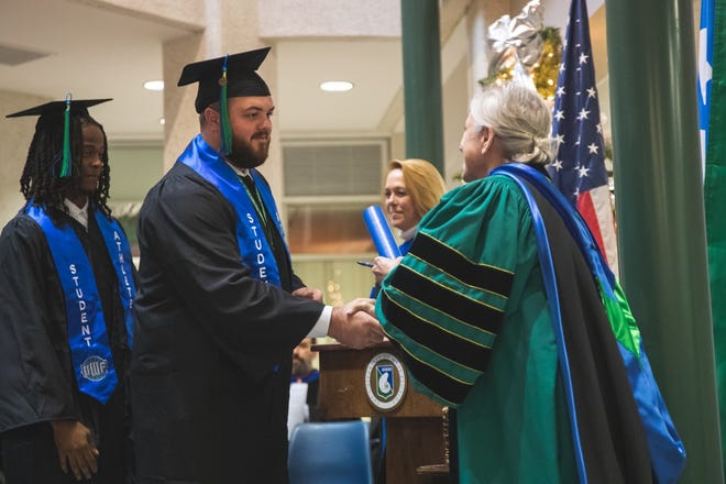 UWF senior center Devin Gibson receives his diploma from UWF president Dr. Martha Saunders in a midweek graduation ceremony on Wednesday, Dec. 11, 2019.